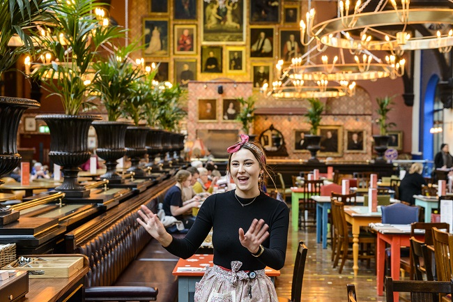 At Cosy Club Lincoln, a smiling woman holds her arms in front of her, smiling.
