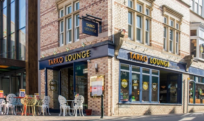 The outside of the Tarko Lounge during the day with tables and chairs outside.